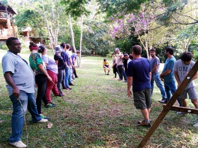 Fotografia com professores alinhados em um gramado participando de atividade da formação na 2ª edição do CPP para academia.